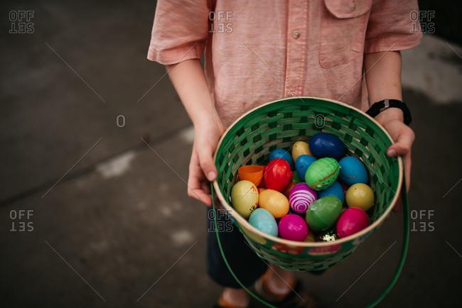 Boy holding plastic eggs in basket