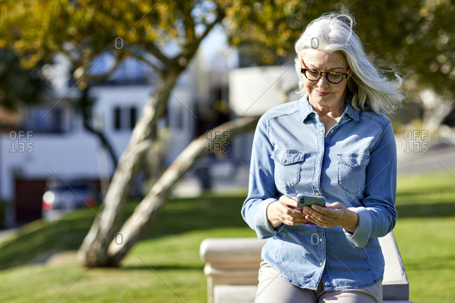 Smiling woman using smart phone while standing by retaining wall in park during sunny day