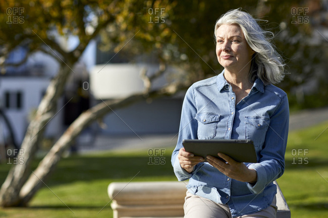 Thoughtful woman holding tablet computer while standing by retaining wall in park during sunny day