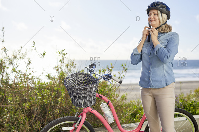 Senior woman wearing cycling helmet while standing against sea during sunny day