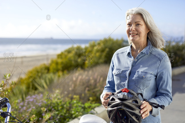 Smiling senior woman holding cycling helmet while standing on road against sky during sunny day