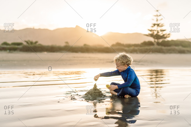 Young child building sandcastle at beach in New Zealand at dusk
