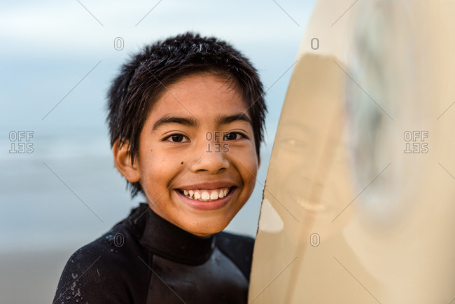 Portrait of happy tween boy holding surfboard