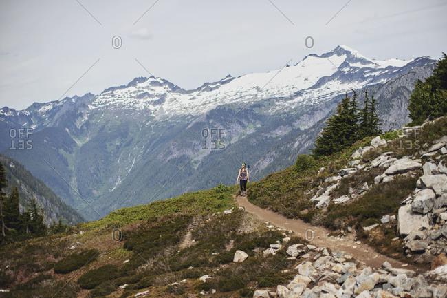 A female hiker walks along a trail in North Cascades National Park.
