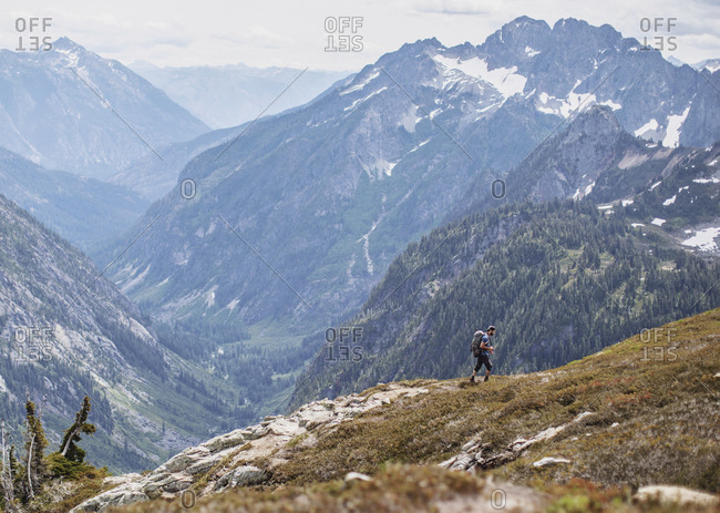 A male hiker walks on a trail with a view in the Cascades, Washington