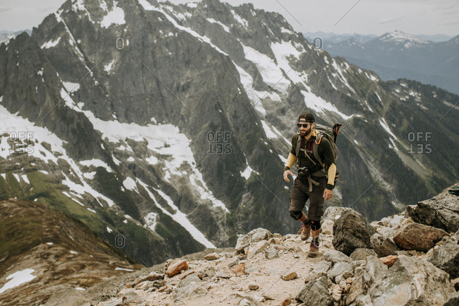 A male hiker walks along a trail in the North Cascades, Washington