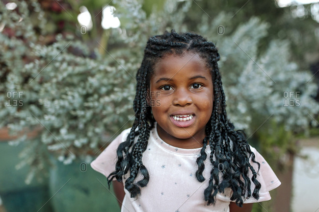 Smiling young black girl with long braids in front of potted plants