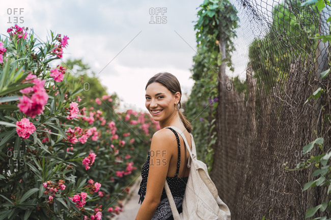 Portrait of smiling young woman with backpack strolling in a park