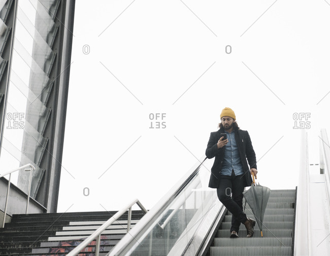 Man with umbrella standing on  escalator looking at smartphone- Berlin- Germany