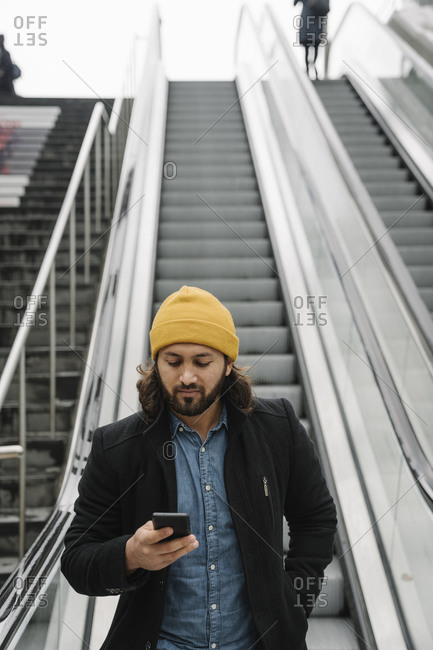 Portrait of bearded man standing on escalator looking at smartphone