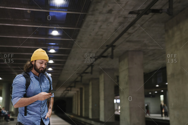 Man waiting at platform using smartphone- Berlin- Germany