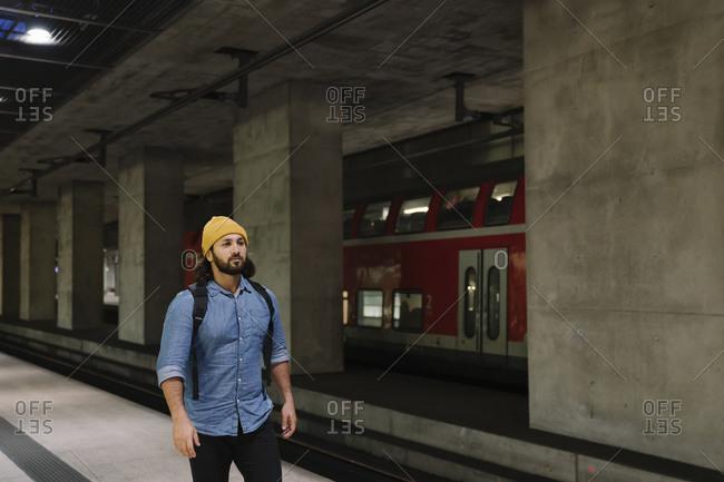 Man with backpack walking at platform- Berlin- Germany
