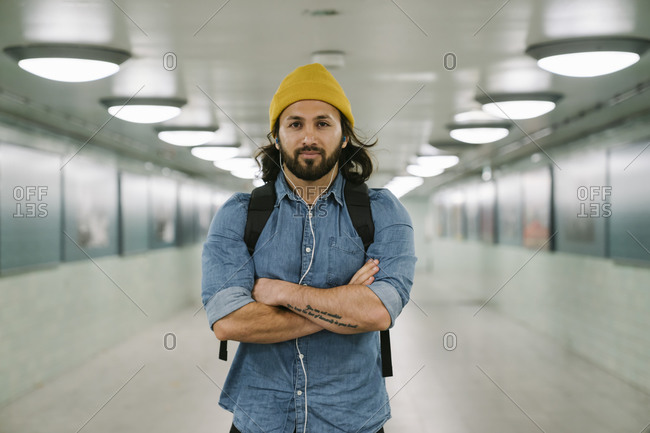 Portrait of bearded man with backpack and earphones in an underpass- Berlin- Germany