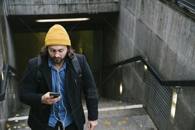 Man with earphones leaving train station on rainy day looking at cell phone