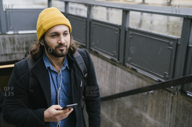 Portrait of man with earphones and cell phone leaving train station on rainy day