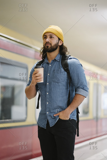 Portrait of man with backpack and coffee to go waiting at platform- Berlin- Germany