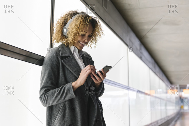 Smiling woman with headphones and smartphone