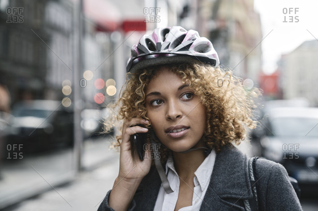 Portrait of woman with bicycle helmet talking on the phone in the city- Berlin- Germany
