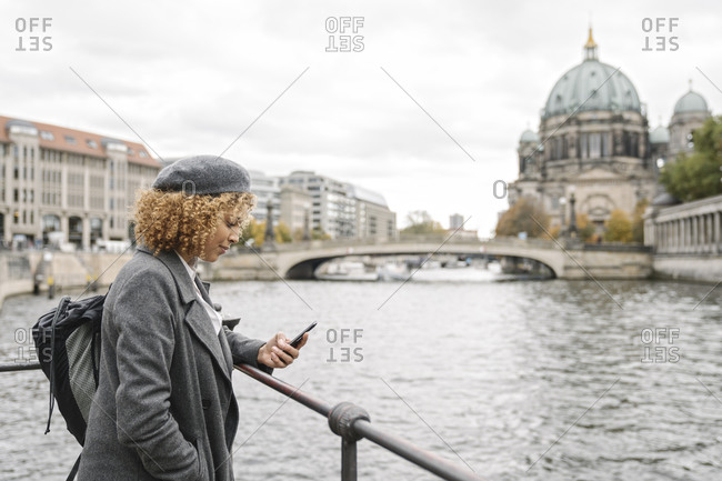 Tourist woman using smartphone in the city with Berlin Cathedral in background- Berlin- Germany