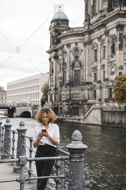Tourist woman using smartphone in the city at Spree river- Berlin- Germany