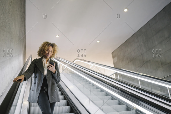 Smiling woman using cell phone on escalator