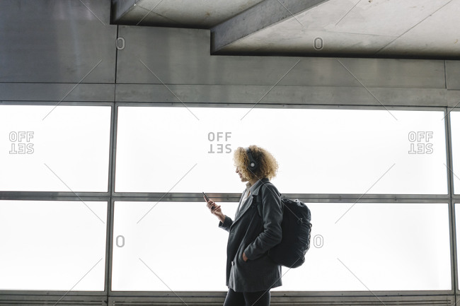 Woman with headphones and backpack using smartphone