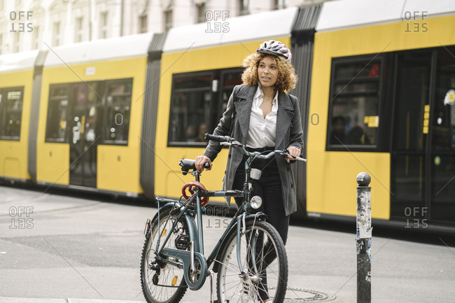 Woman with bicycle commuting in the city- Berlin- Germany