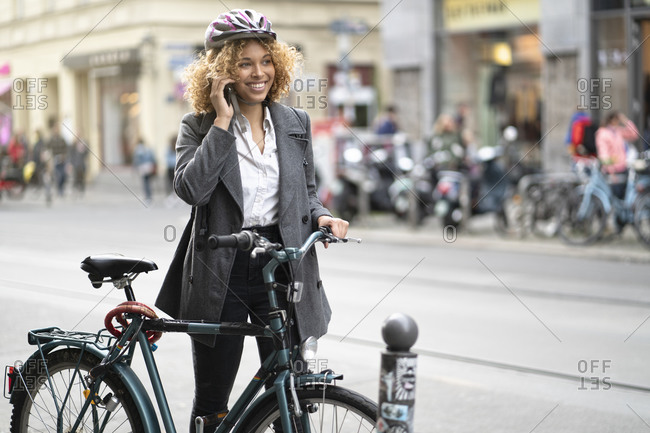 Smiling woman with bicycle talking on the phone in the city- Berlin- Germany