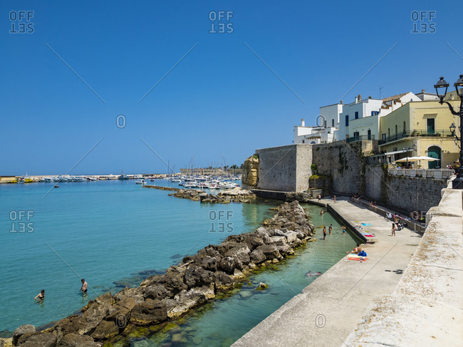 June 8, 2019: Italy- Province of Lecce- Otranto- People relaxing along shore of coastal town in summer