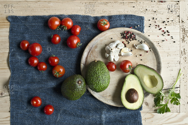 Directly above shot of avocados with tomatoes and spices on wooden table