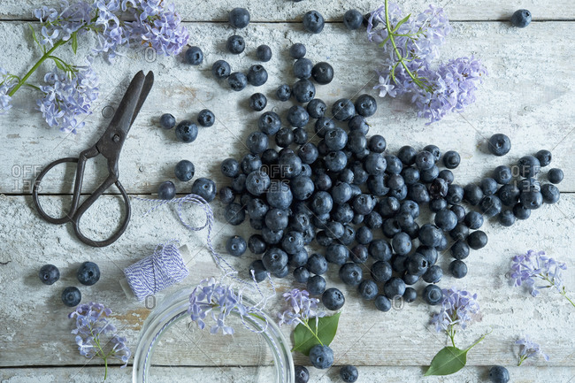 Directly above shot of blueberries with lilac and scissors on wooden table