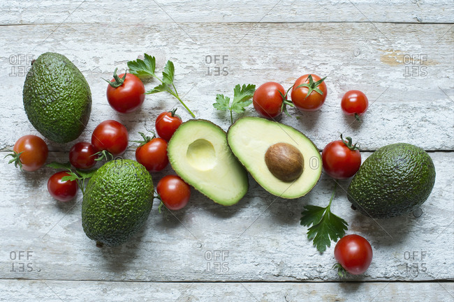 Directly above shot of avocados with tomatoes and parsley on wooden table