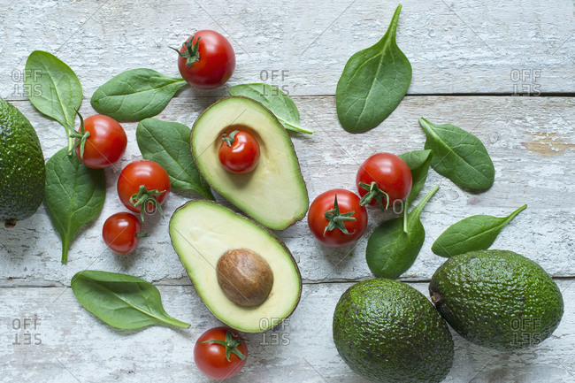 Directly above shot of avocados with tomatoes and spinach on wooden table