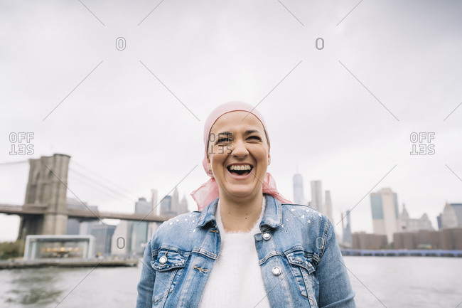 Portrait of laughing woman with cancer bandana at Brooklyn Bridge in New York- USA