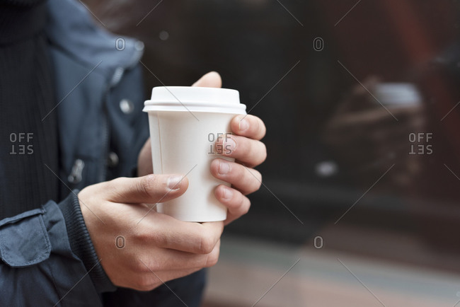 Young man holding a takeaway coffee outdoors