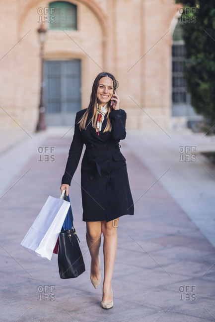 Portrait of happy young woman on the phone walking in the city with shopping bags