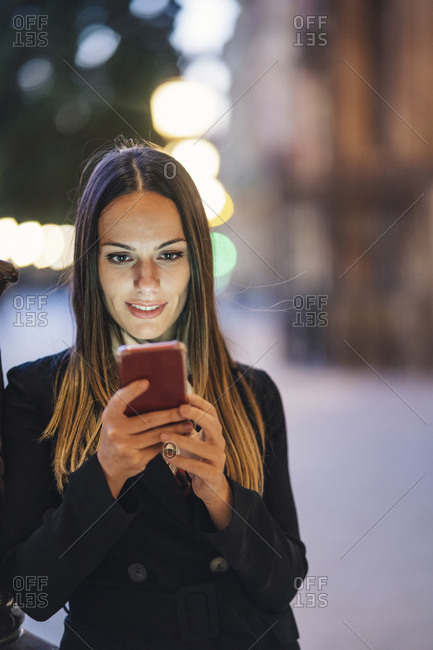 Portrait of smiling young woman leaning against lamp pole in the evening looking at cell phone