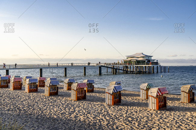 July 21, 2019: Germany- Schleswig-Holstein- Timmendorf- Strandkorb beach-chairs on sandy coastal beach with pier in background