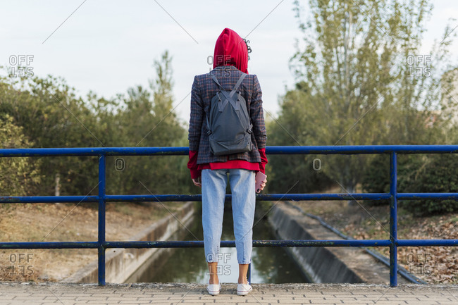 Back view of young woman with backpack and mobile phone standing on a bridge