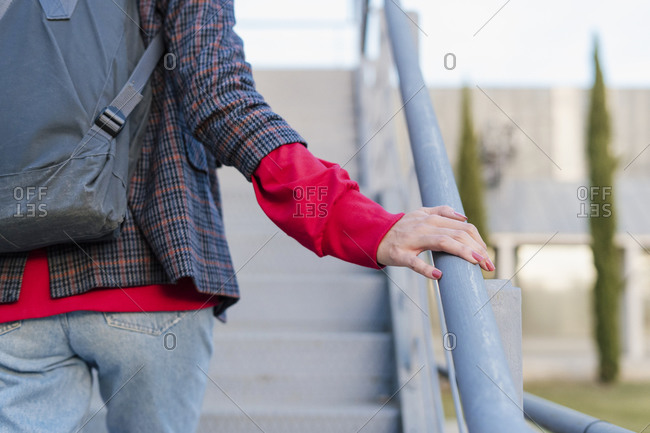 Crop view of young woman with backpack walking upstairs