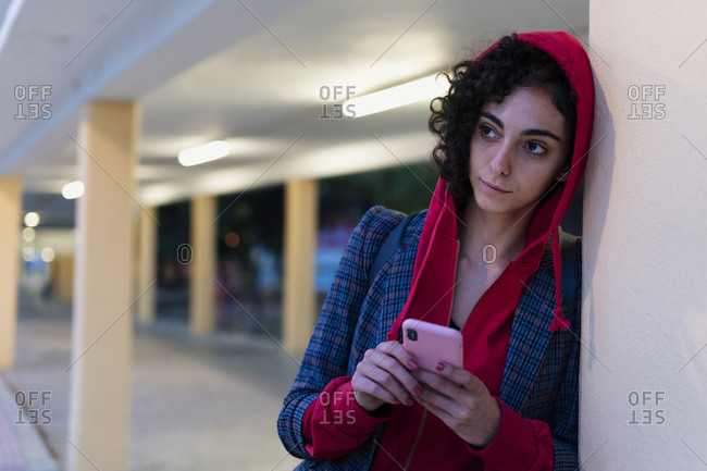 Portrait of young woman with mobile phone in the evening