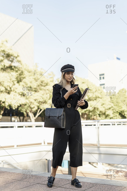 Young blond businesswoman wearing black hat and holding laptop bag and using smartphone