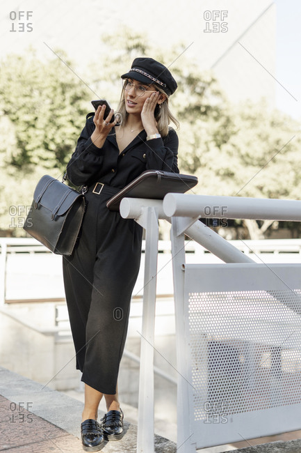 Young blond businesswoman wearing black hat and using smartphone