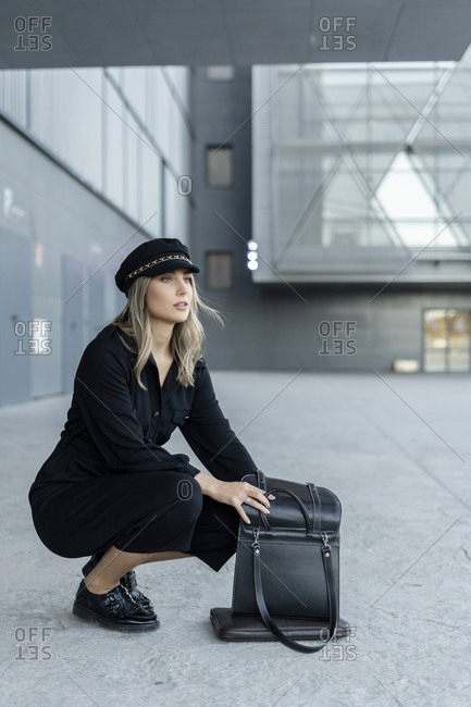 Young blond businesswoman wearing sailor's cap and searching in her bag
