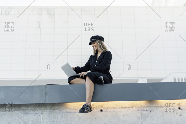 Young blond businesswoman wearing black sailor's cap and using laptop- sitting on a wall