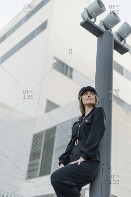 Young blond businesswoman wearing black sailor's cap and looking sideways- leaning on a lamp pole- low angle view