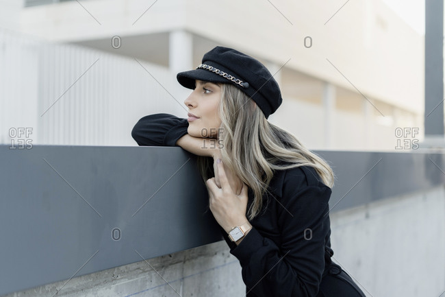 Young blond businesswoman wearing black sailor's cap and looking sideways
