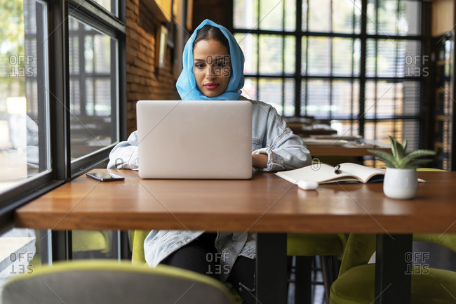 Businesswoman wearing turquoise hijab in a cafe and working- using laptop