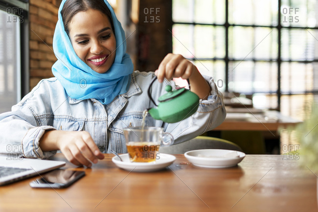 Businesswoman wearing turquoise hijab in a cafe and working- pouring tea