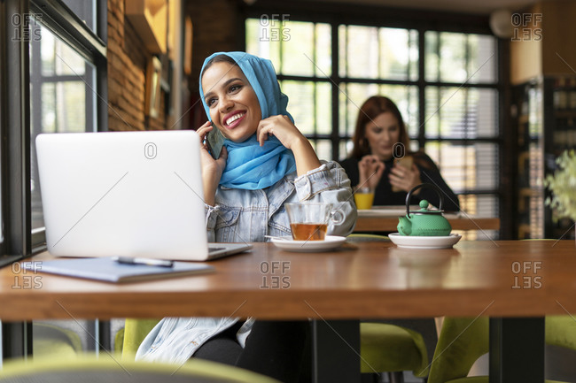 Businesswoman wearing turquoise hijab in a cafe and working with her laptop- on the phone